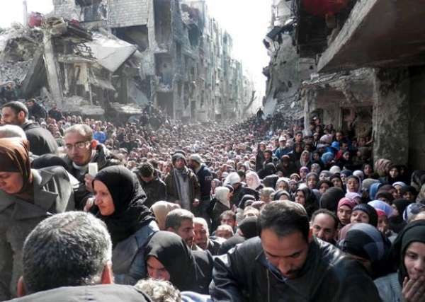Palestinians waiting for food at the Yarmouk camp in Damascus a month ago -- in a photo released yesterday by United Nations.